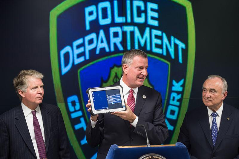 El comisario de policía William J. Bratton y el Abogado del Distrito de  Manhattan Cyrus R. Vance, Jr miran con ojos golosos la wintablet que sujeta su alcalde.