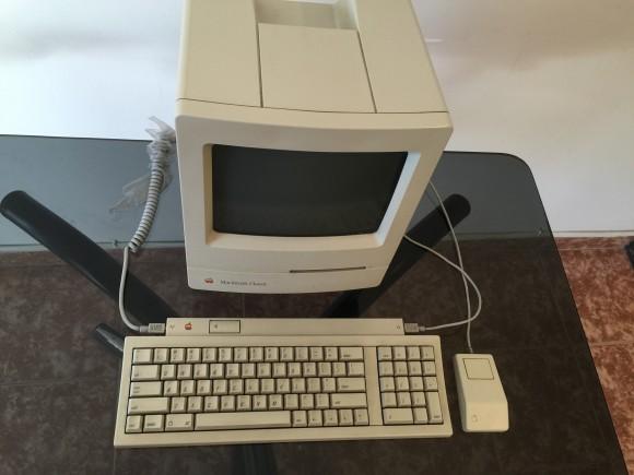 Una mejor vista del teclado, el Macintosh y el mouse. Note que el mouse esta conectado del lateral derecho del teclado, mientras que en el lateral izquierdo esta el cable que conecta el teclado con la computadora. Si lo configura para zurdos el uso de los conectores se invierte.